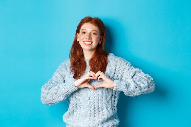 ハートのサインを示すセーターのかわいい赤毛の女の子、私はあなたのジェスチャーを愛し、カメラに微笑んで、青い背景に立っています。