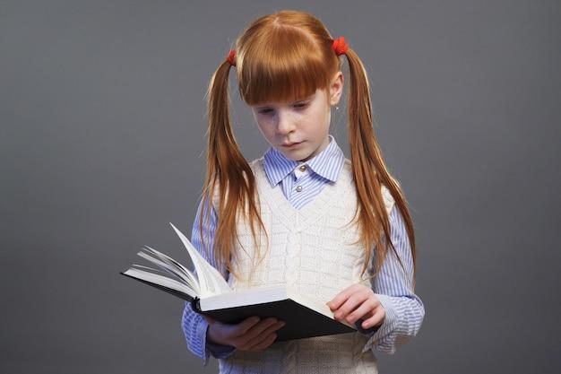 귀여운 빨간 머리 소녀는 책을 읽고 있습니다