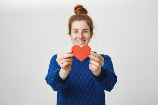 Милая рыжая девушка показывает жест сердца. концепция отношений и любви