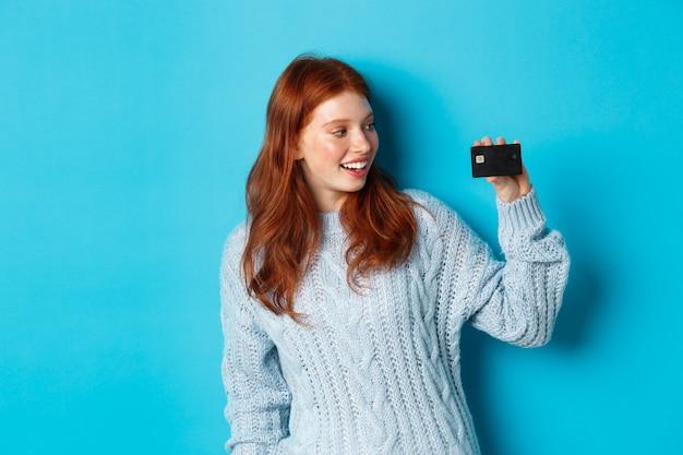 Ragazza carina rossa in maglione che mostra la carta di credito, sorride alla macchina fotografica, in piedi su sfondo blu