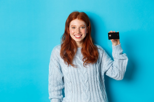 Cute redhead girl in sweater showing credit card, smiling at camera, standing over blue background.
