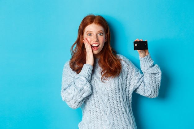 Cute redhead girl in sweater showing credit card, smiling at camera, standing over blue background
