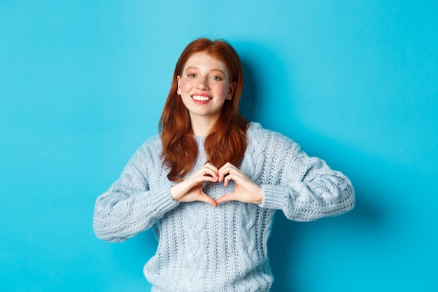 Cute redhead girl in sweater showing heart sign, i love you gesture, smiling at camera, standing against blue background.