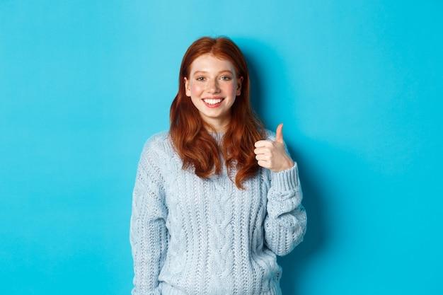 Carina ragazza rossa in maglione che mostra pollice in su, mi piace e concorda, sorride compiaciuta, in piedi su sfondo blu