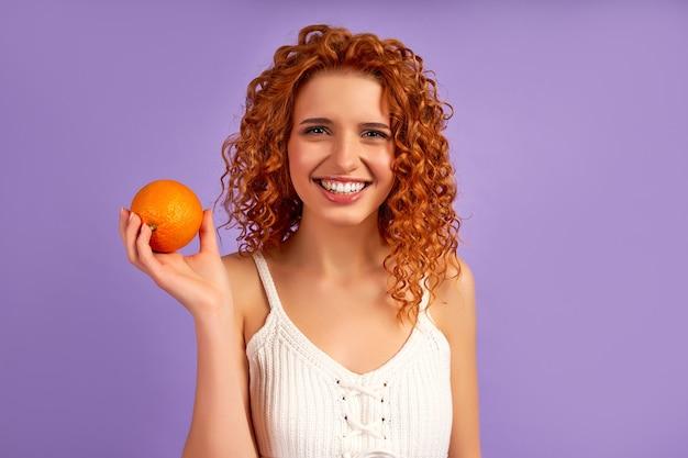 보라색 벽에 고립 된 오렌지를 들고 곱슬 머리와 귀여운 빨간 머리 소녀. 적절한 영양. 건강한 생활.