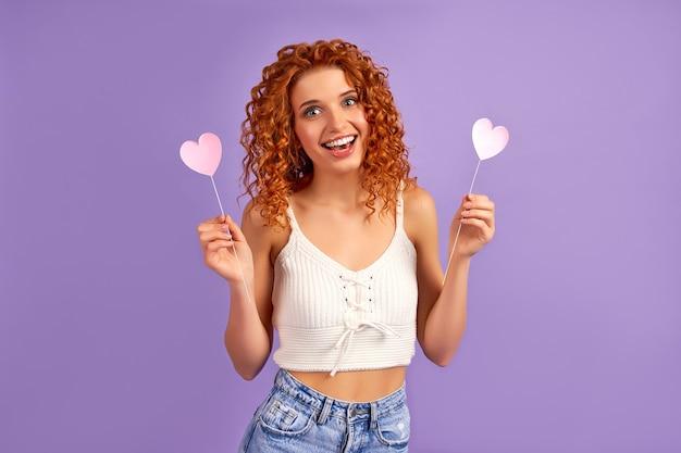 紫色の壁に分離された棒にバレンタインの心を保持しているカールを持つかわいい赤毛の女の子。