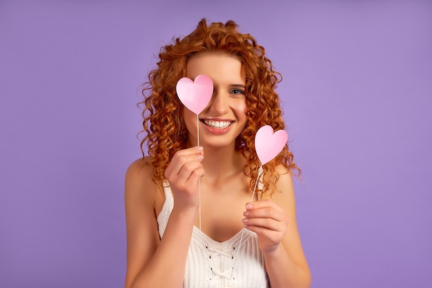 Cute redhead girl with curls holding valentine hearts on sticks isolated on purple wall.