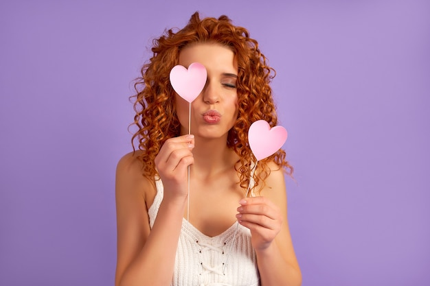 Cute redhead girl with curls holds valentine hearts on sticks and sends a kiss isolated on purple wall.