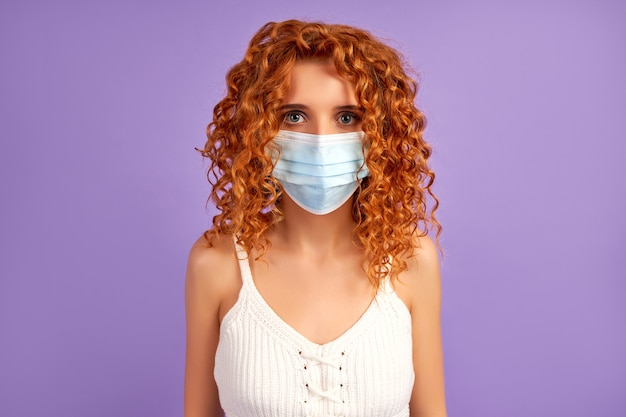 Cute redhead girl with curls in protective medical mask isolated on purple wall.
