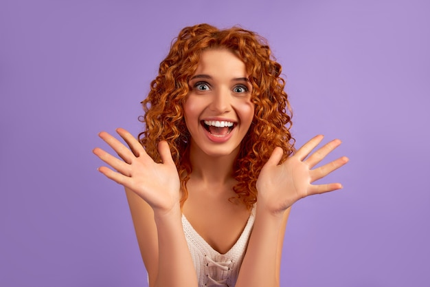 カールのかわいい赤毛の女の子は、紫色の壁に孤立してショックを受けた驚きの感情を示しています。