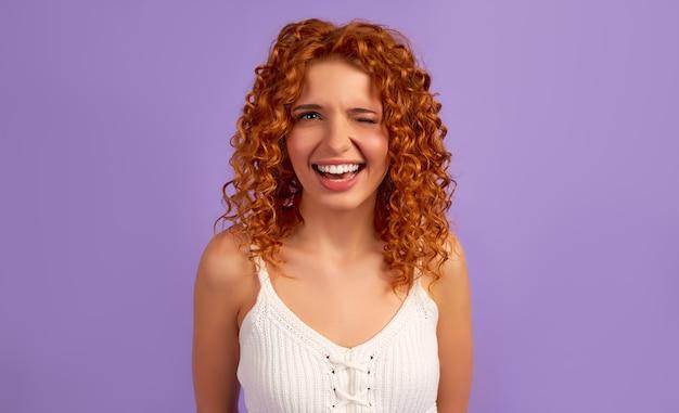 紫色の壁に分離されたカールウィンクとかわいい赤毛の女の子。