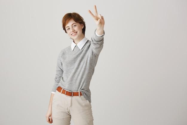 白い壁にポーズをとって短い散髪のかわいい赤毛の女の子