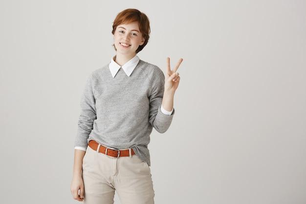 Ragazza carina rossa con taglio di capelli corto in posa contro il muro bianco