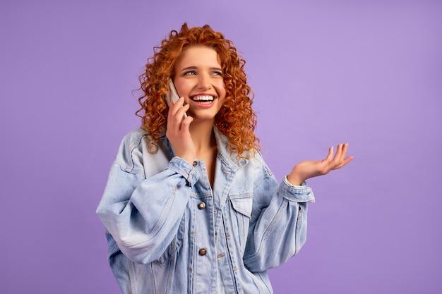보라색 벽에 고립 된 전화 통화 데님 재킷에 곱슬 머리와 귀여운 빨간 머리 hipster 소녀.