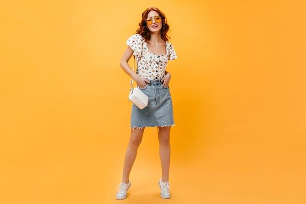 Милая рыжая дама в юбке и стильной футболке с улыбкой позирует на оранжевом фоне.