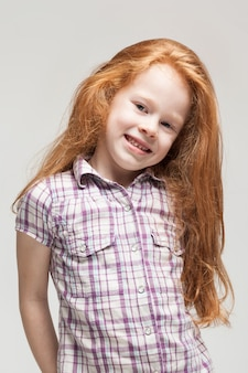 Cute redhead little girl in plaid shirt, bright blue trousers and white boots