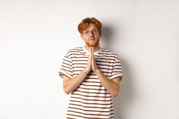 助けを求めて、懇願し、カメラに固執し、好意を求めて、白い背景を懇願する眼鏡をかけたかわいい赤毛の男。