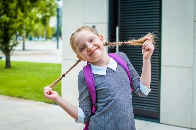 귀여운 빨간 머리 여학생이 웃고, 땋은 머리를 잡고 있습니다. 학교에 다시 행복.