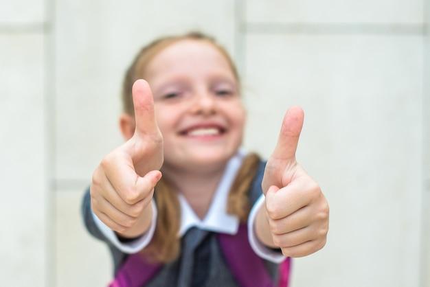 귀여운 빨간 머리 여학생은 웃고, 같은 손을 보여줍니다. 학교에 다시 행복. 선택적 초점