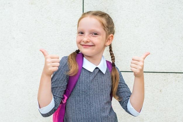 귀여운 빨간 머리 여학생은 웃고, 같은 손을 보여줍니다. 학교에 다시 행복.