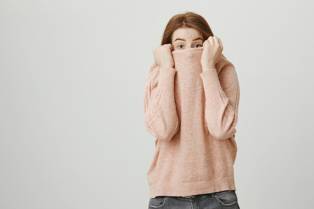 Cute redhead teenage girl hide face over sweater, peeking