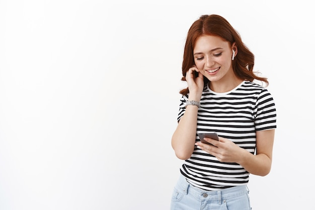 Cute redhead teenage girl in striped t-shirt put on wireless earphones, hold smartphone, smiling relaxed and happy mobile phone display, pick song on internet music platform, listen favorite podcast