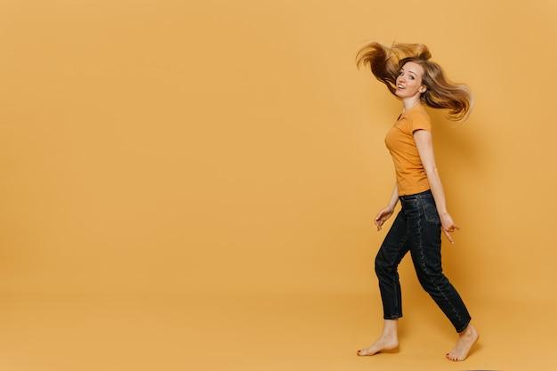 Милая рыжая женщина, одетая в оранжевую футболку и черные джинсы, идет с развевающимися волосами, широко улыбается, указывая на ее голые ноги, на желтый фон. концепция магазинов и продаж.
