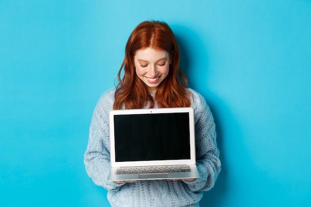 Симпатичная рыжая женщина в свитере показывает и смотрит на экран ноутбука с довольной улыбкой, демонстрируя что-то в интернете, стоя на синем фоне