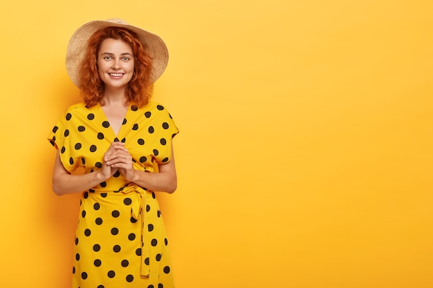 Cute redhead woman posing in yellow polka dress and straw hat