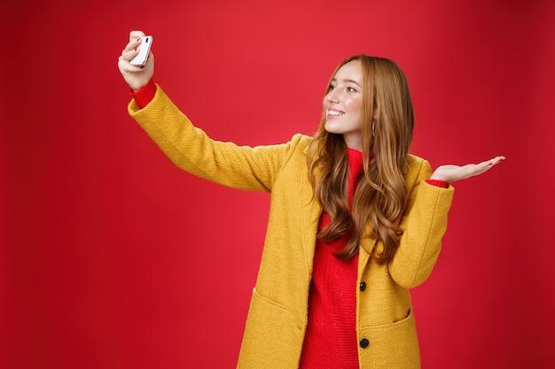 Cute redhead woman walking in park deciding take selfie near beatiful scenery or cute animal extendi...