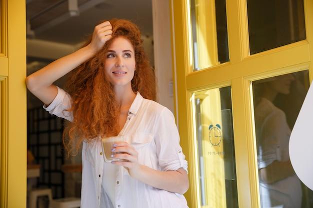 Donna rossa carina con i capelli lunghi, tenendo la tazza di caffè