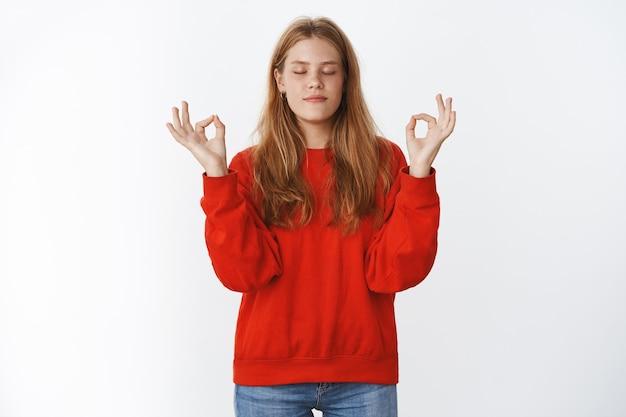 Милая расслабленная и мирная очаровательная светловолосая женщина с веснушками, стоящая в позе лотоса с жестами дзэн, медитирующая с закрытыми глазами, достигая нирваны над серой стеной