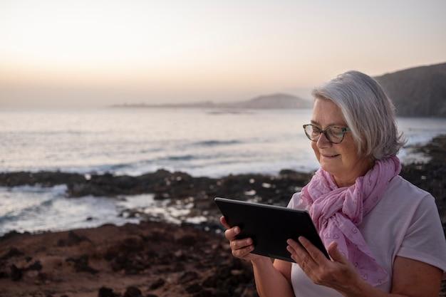 태블릿으로 그물을 서핑하는 해변 근처에 앉아 있는 귀여운 편안한 고위 여성 회색 머리. 황혼의 빛. 백그라운드에서 산과 바다입니다.