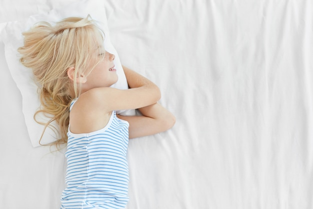Cute restful child lying on white pillow in bed, sleeping pleasantly, having good dreams and happy expression. lovely small kid resting on white bed cover, having good night. childhood concept