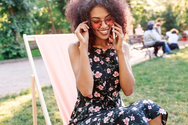Ragazza romantica sveglia che utilizza smartphone mentre rilassandosi nel parco di estate con i suoi amici sul picnic.