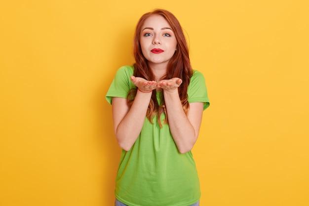Милая романтическая рыжеволосая женщина в зеленой футболке стоит и отправляет любовный воздушный поцелуй в камеру, демонстрируя привязанность