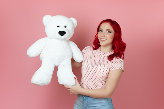 Cute, romantic woman with red hair gently cuddles a large white teddy bear