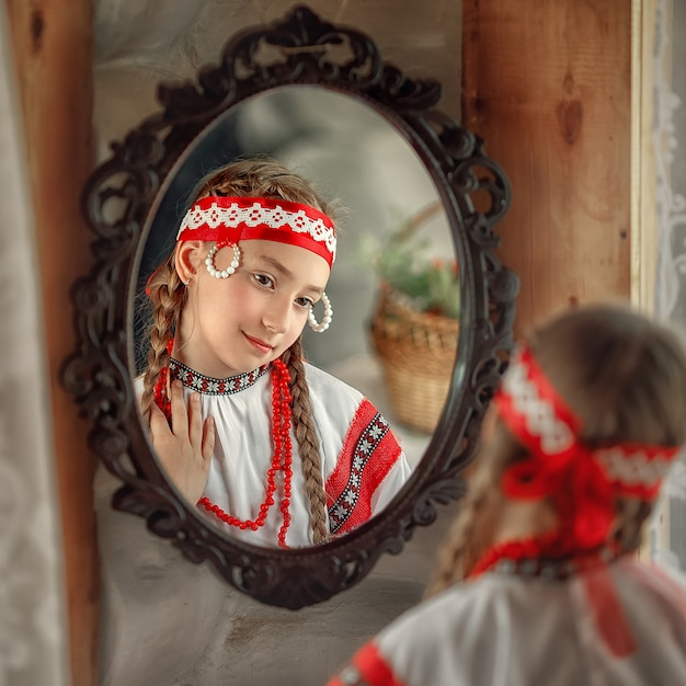 民族衣装のかわいいロシアの女の子が鏡を見る