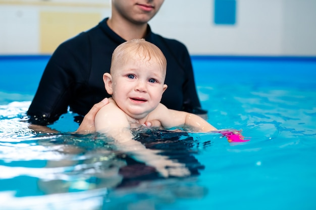 Cute sad baby boy learning to swim in special pool for little children