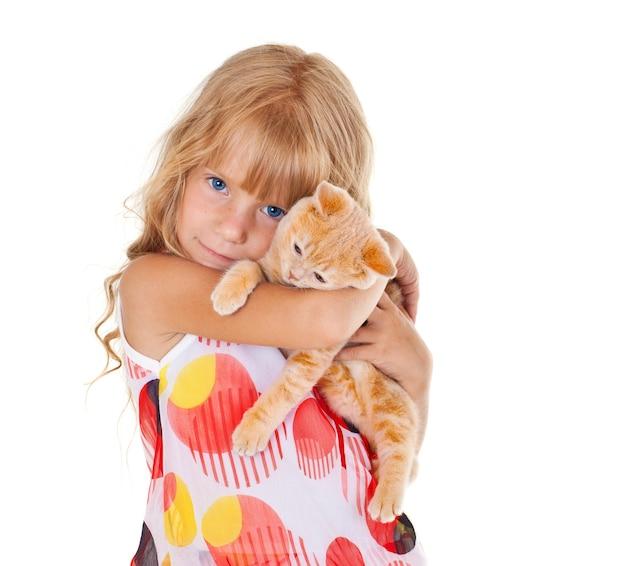 Милая грустная девушка обнимает маленькую кошку на белом фоне