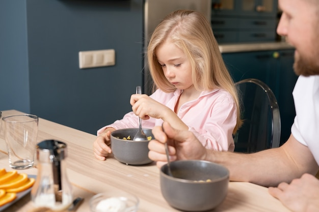 Cute sad girl putting spoon into bowl with muesli while having breakfast by table in the kitchen with her father sitting near by
