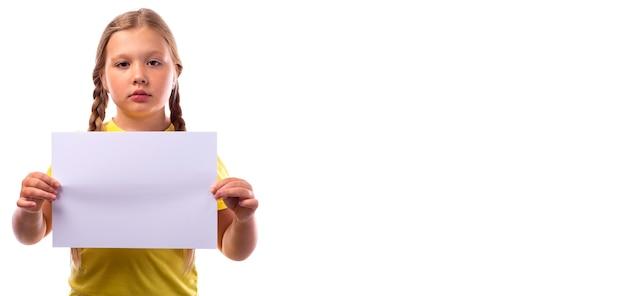 금발 머리를 가진 귀여운 슬픈 소녀, 두 개의 땋은 머리로 땋아 흰색 배경에 흰색 종이를 들고