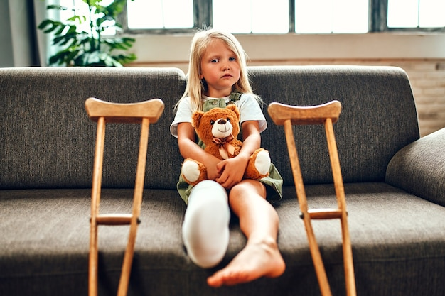 A cute sad little girl with a broken leg in a cast, sits on the couch hugging a teddy bear at home. there are crutches near the sofa for quick rehabilitation.