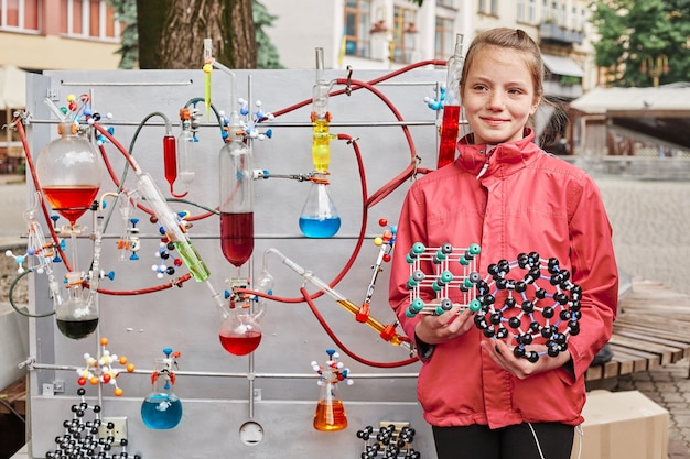 Cute school-age girl poses near a model with a chemical process