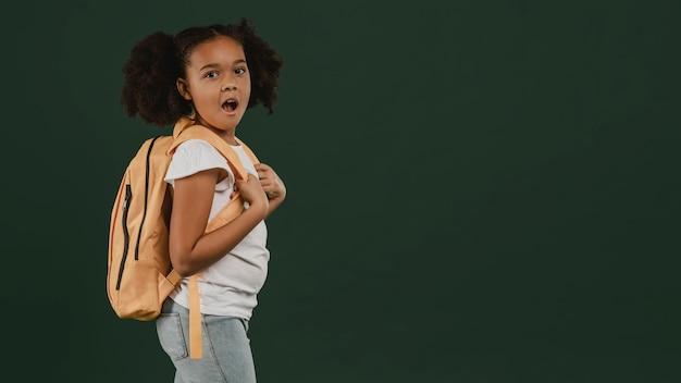 かわいい女子高生と彼女のバックパックのコピースペース