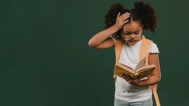 Cute school girl reading a book