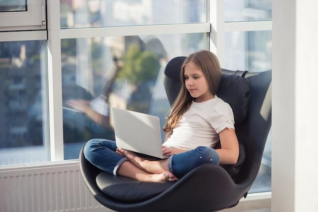 Милая школьница сидит в уютном кресле с ноутбуком в кожаном черном кресле