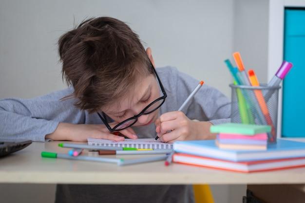 机に座ってメモを書いて家で勉強している眼鏡のかわいい学校の生徒の子供の男の子。