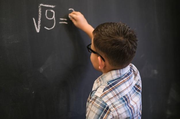 かわいい男子生徒は、黒い黒板で数学の問題を解決します。平方根の計算