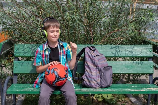 Милый школьник, одетый в повседневную одежду, слушает музыку в наушниках, сидит на скамейке с футбольным мячом. снова в школу концепции